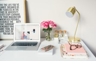 Home office desk with laptop, books, glasses, roses and lamp